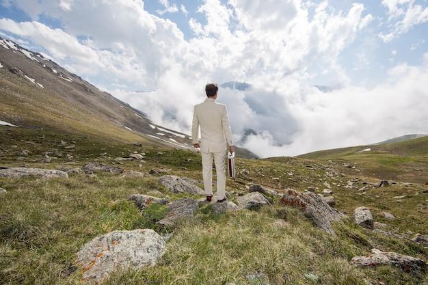 Homme d'affaires en costume blanc au sommet de la montagne