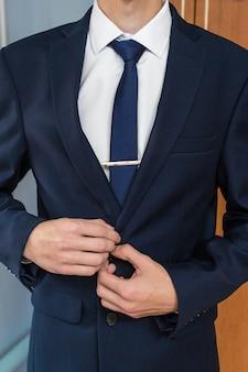 Homme d'affaires en costume bleu attachant la cravate. tenue décontractée élégante. homme se prépare pour le travail. le matin du marié