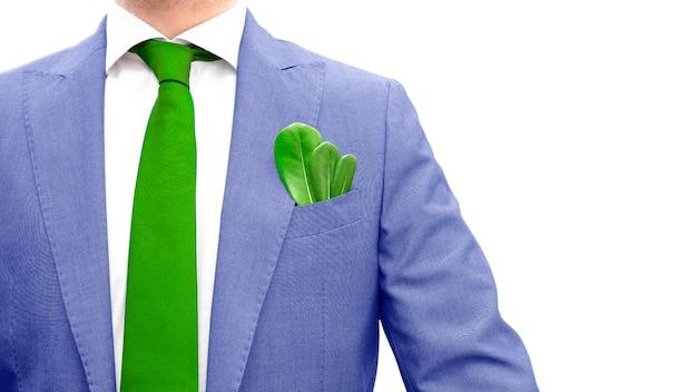 Homme d'affaires en costume bleu, cravate verte et feuille verte dans la poche isolée. conscience et conscience de l'environnement social, concept écologique. espace copie