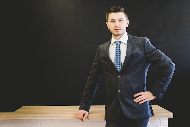 Homme d'affaires en costume close-up dans une pose confiante isolée sur un tableau noir et une table en bois