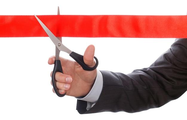 Homme d'affaires en costume coupant le ruban rouge avec une paire de ciseaux