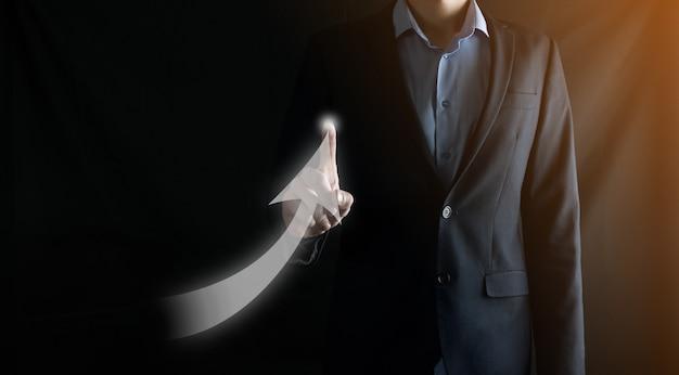 Homme d'affaires en costume dessine une flèche vers le haut avec son doigt sur fond sombre. concept de croissance financière.