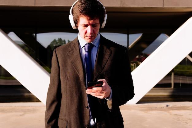 Homme d'affaires en costume écoutant de la musique avec des écouteurs en regardant un smartphone. concept technologique