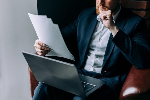 Un homme d'affaires en costume est assis dans un fauteuil avec un ordinateur portable et analyse les informations d'un papier.