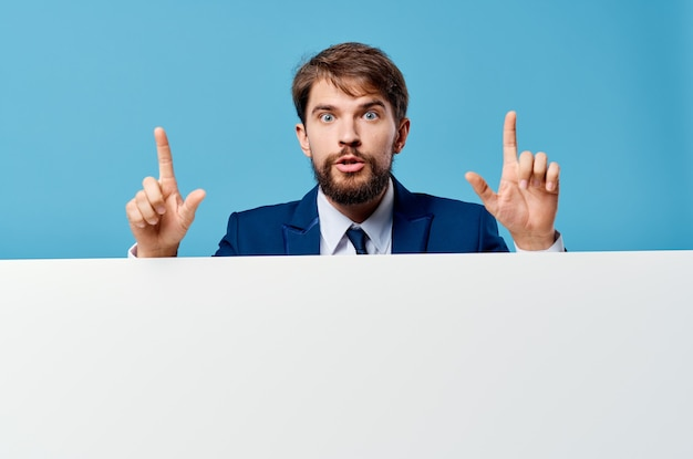 Homme d'affaires en costume faisant des gestes avec le mur bleu de présentation de bannière de mains.