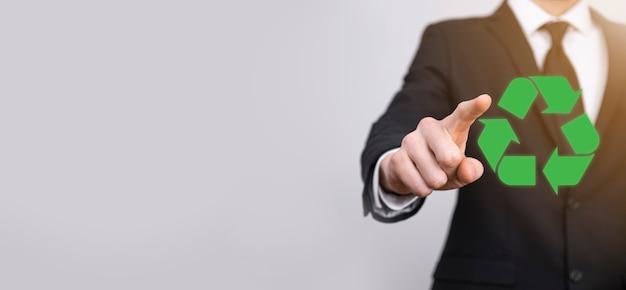 Homme d'affaires en costume sur fond gris détient une icône de recyclage, signe dans ses mains. concept d'écologie, d'environnement et de conservation.