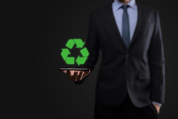Homme d'affaires en costume sur fond sombre détient une icône de recyclage, signe dans ses mains. concept d'écologie, d'environnement et de conservation. lumière bleue rouge néon