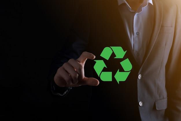 Homme d'affaires en costume sur fond sombre détient une icône de recyclage, signe dans ses mains. concept d'écologie, d'environnement et de conservation. lumière bleue rouge néon.