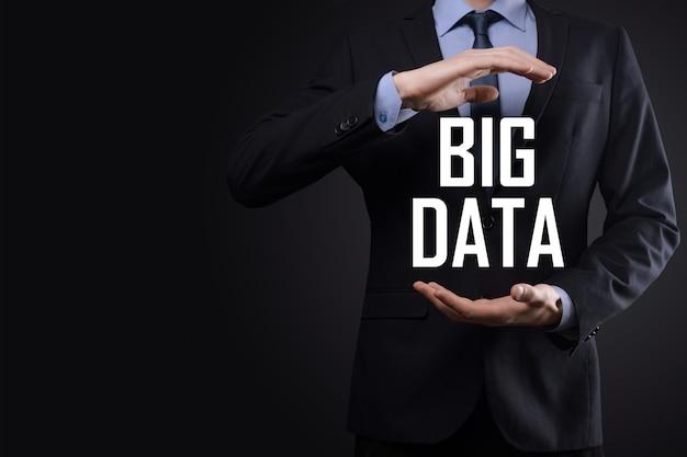 Un homme d'affaires en costume sur fond sombre détient l'inscription big data. concept de serveur en ligne de réseau de stockage. réseau social ou représentation analytique d'entreprise.