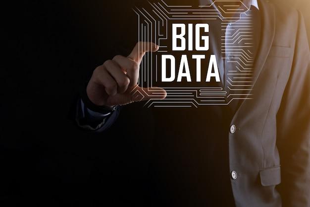 Un homme d'affaires en costume sur fond sombre détient l'inscription big data. réseau de stockage en ligne server concept.réseau social ou représentation analytique d'entreprise