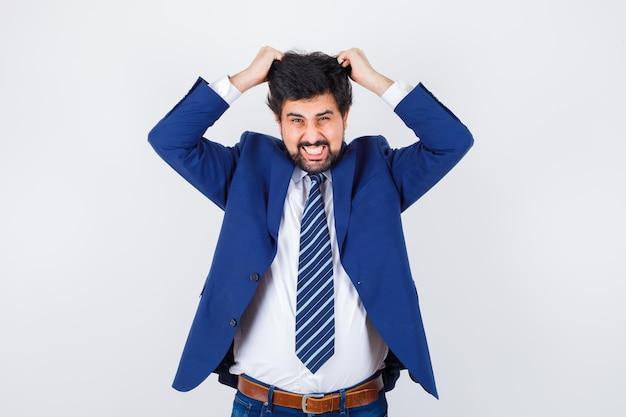 Homme d'affaires en costume formel se grattant la tête et ayant l'air épuisé, vue de face.