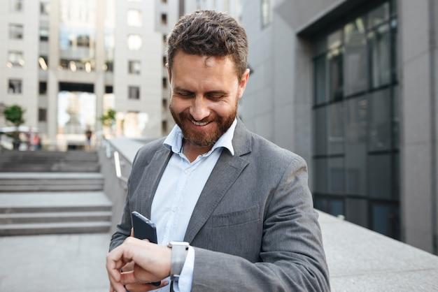 Homme d'affaires en costume gris tenant un téléphone portable et regardant smartwatch, tout en ayant une pause après avoir travaillé au bureau