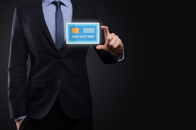 Homme d'affaires en costume main tenant l'icône de carte de crédit vierge montrant pour le service bancaire et financier concept