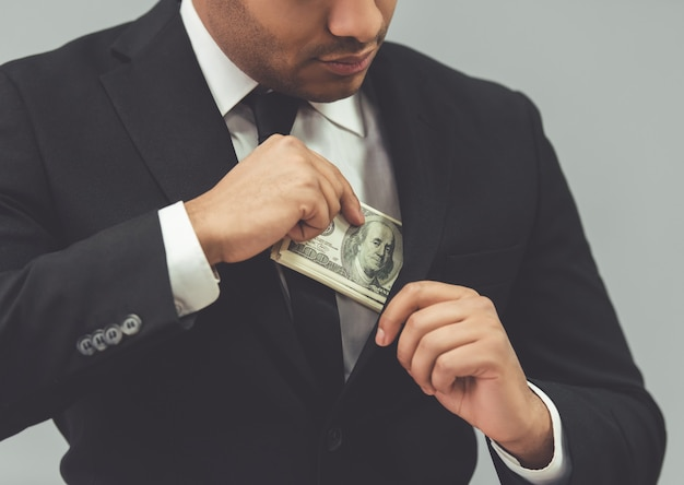 Un homme d'affaires en costume met de l'argent dans sa poche intérieure.