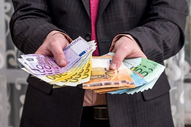 Homme d'affaires en costume montrant les gains, les billets en euros