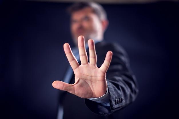 Homme d'affaires en costume montrant un panneau d'arrêt avec les mains devant un fond noir