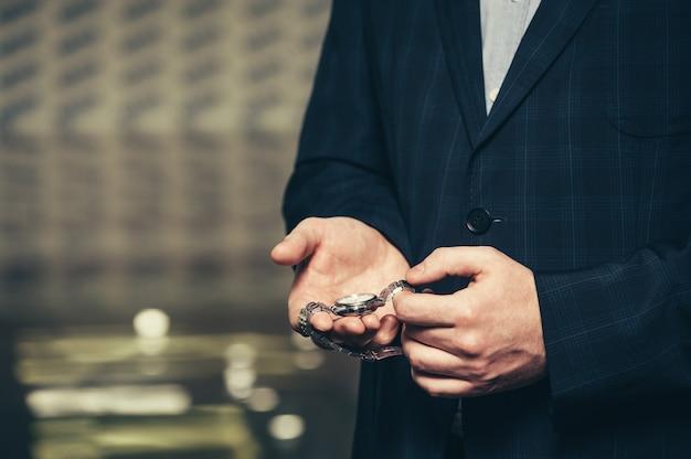 Homme d'affaires en costume montre sa montre-bracelet.