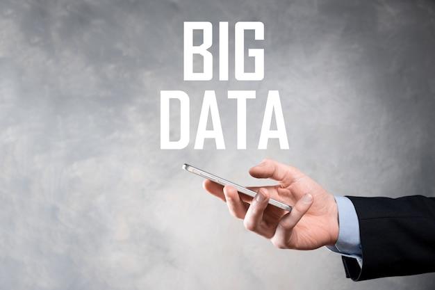Homme d'affaires en costume sur un mur sombre détient l'inscription big data. concept de serveur de réseau de stockage en ligne représentation de réseau social ou d'analyse commerciale.