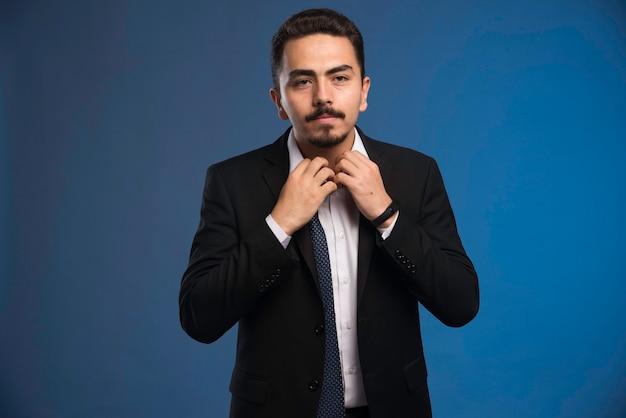 Homme d'affaires en costume noir bouton d'ouverture de sa chemise.