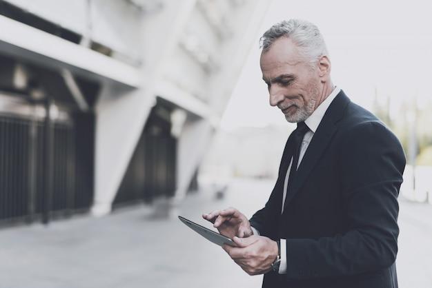Homme d'affaires en costume noir cherche sur une tablette