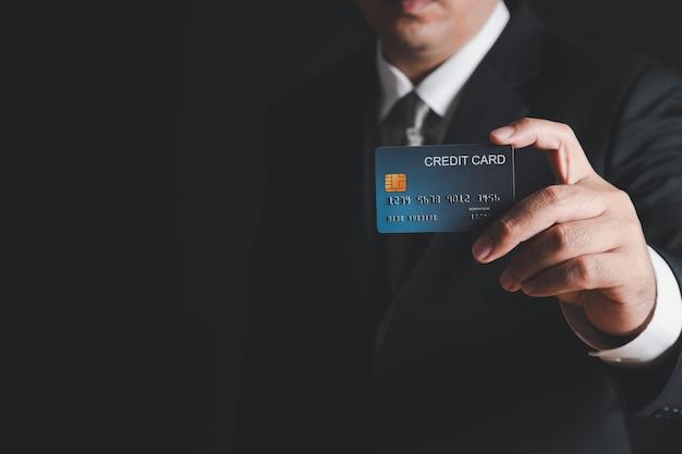 Homme d'affaires en costume noir et cravate grise montrant la carte de crédit sur le mur noir. concept bancaire de paiement