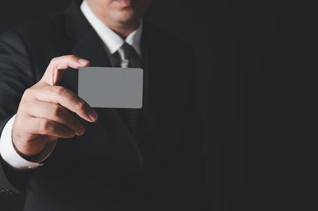 Homme d'affaires en costume noir et cravate grise montrant une carte grise sur un mur noir. concept bancaire de paiement