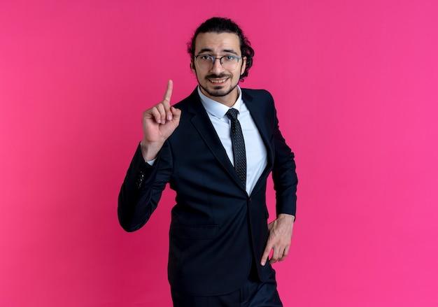 Homme d'affaires en costume noir et lunettes à l'avant montrant l'index souriant ayant une excellente idée debout sur un mur rose