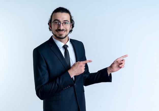 Homme d'affaires en costume noir et lunettes à l'avant en souriant joyeusement en pointant avec l'index sur le côté debout sur un mur blanc