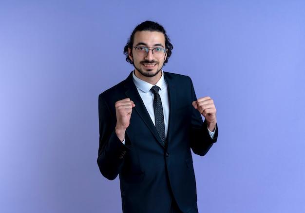 Homme d'affaires en costume noir et lunettes à l'avant souriant joyeusement serrant les poings heureux et excité debout sur le mur bleu