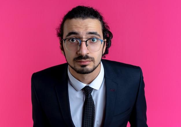 Homme d'affaires en costume noir et lunettes à l'avant surpris avec les yeux grands ouverts debout sur le mur rose