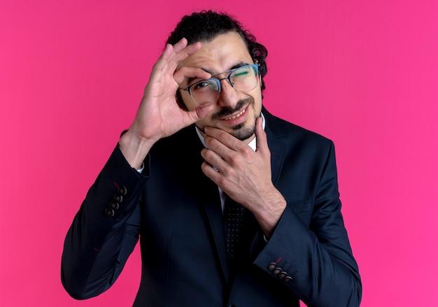 Homme d'affaires en costume noir et lunettes faisant signe ok à l'avant avec le sourire à travers ce panneau debout sur un mur rose