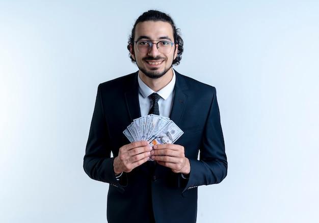 Homme d'affaires en costume noir et lunettes montrant de l'argent à l'avant souriant joyeusement debout sur un mur blanc