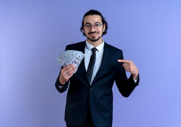 Homme d'affaires en costume noir et lunettes montrant de l'argent pointant avec le doigt dessus souriant joyeusement debout sur le mur bleu