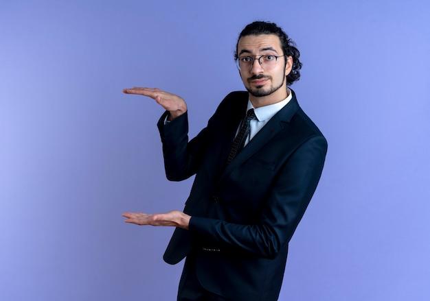 Homme d'affaires en costume noir et lunettes montrant le geste de taille avec les mains, symbole de mesure debout sur le mur bleu