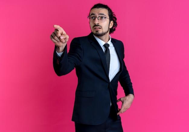 Homme d'affaires en costume noir et lunettes pointant avec le doigt sur le côté à la surprise debout sur le mur rose