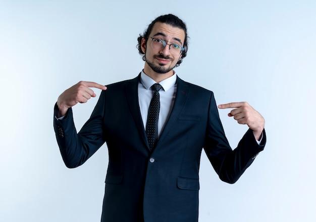 Homme d'affaires en costume noir et lunettes pointant avec l'index vers lui-même à l'avant avec le sourire sur le visage debout sur un mur blanc