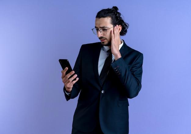 Homme d'affaires en costume noir et lunettes regardant l'écran de son smartphone avec une expression de confusion debout sur un mur bleu
