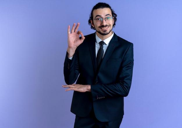 Homme d'affaires en costume noir et lunettes regardant vers l'avant souriant joyeusement montrant signe ok debout sur mur bleu
