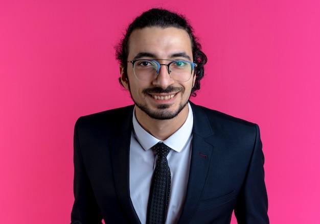 Homme d'affaires en costume noir et lunettes regardant vers l'avant souriant avec visage heureux debout sur un mur rose