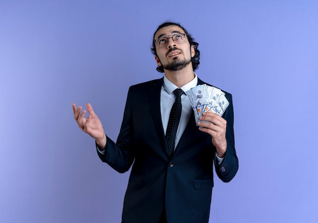 Homme d'affaires en costume noir et lunettes tenant de l'argent à la perplexité debout sur le mur bleu
