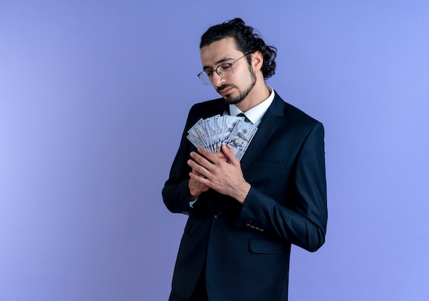 Homme d'affaires en costume noir et lunettes tenant de l'argent en se sentant reconnaissant avec les yeux fermés debout sur le mur bleu