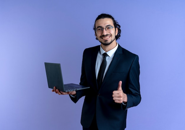 Homme d'affaires en costume noir et lunettes tenant un ordinateur portable à l'avant souriant montrant les pouces vers le haut debout sur le mur bleu
