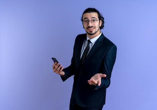 Homme d'affaires en costume noir et lunettes tenant le smartphone à l'avant avec le bras comme demandant debout sur le mur bleu