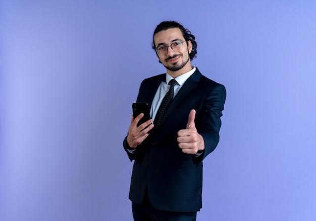 Homme d'affaires en costume noir et lunettes tenant le smartphone montrant les pouces vers le haut souriant confiant debout sur le mur bleu