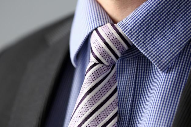 Homme d'affaires en costume noir mis cravate closeup