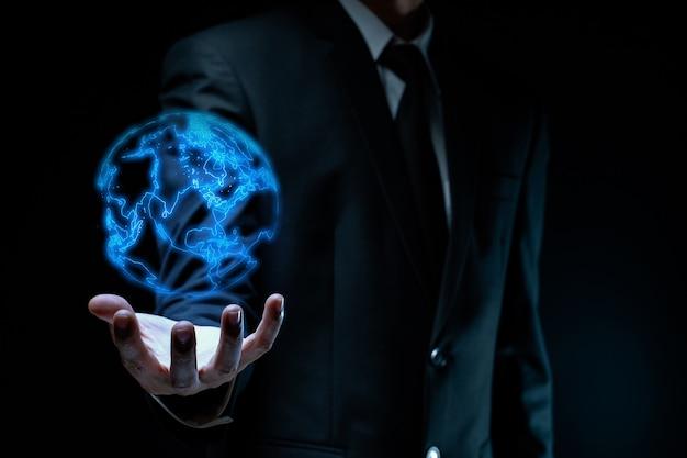 Homme d'affaires en costume noir montrant l'effet d'hologramme de carte du monde.