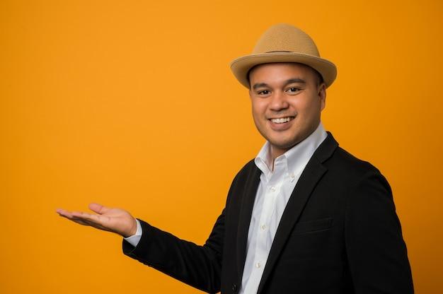 Homme d'affaires en costume noir pointant la main à côté isolé sur jaune