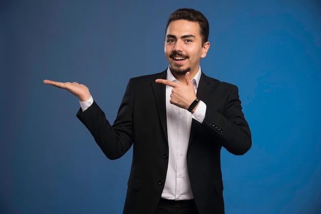 Homme d'affaires en costume noir pointant vers quelque chose.