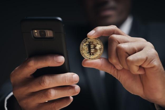Homme d'affaires en costume noir tenant un bitcoin doré à l'aide d'un smartphone avec un graphique de trading bitcoin à l'écran pour échanger des crypto-monnaies, des financements alternatifs et un concept d'investissement.