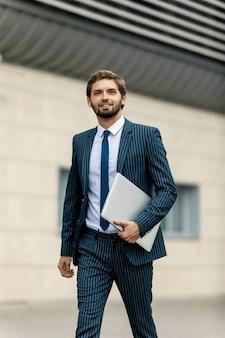 Homme d'affaires en costume avec un ordinateur portable à la main va travailler sur la route de l'entrée d'un immeuble de bureaux en verre.